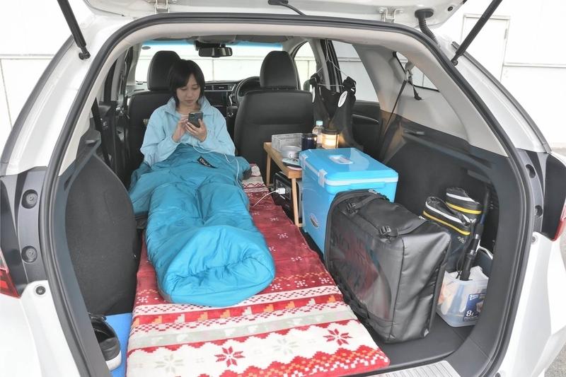 Hondaシャトルの荷室を車中泊仕様にフラットにしたところに、お昼寝マットを敷いて女性が寝袋に入って寝ている横に、クーラーボックスやミニテーブル、リュックなどの荷物が置いてある写真