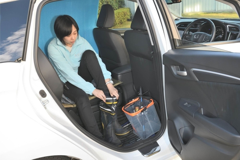 後部座席の片側だけを倒して車中泊仕様にしたHondaシャトルの後部座席で長靴を脱いでいる女性の写真
