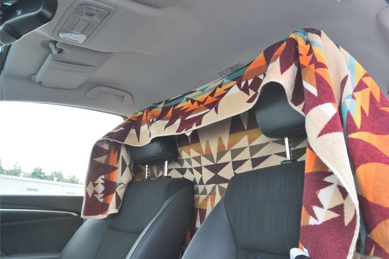 運転席と助手席のヘッドレストを伸ばしたところに大きなタオルをかけている写真