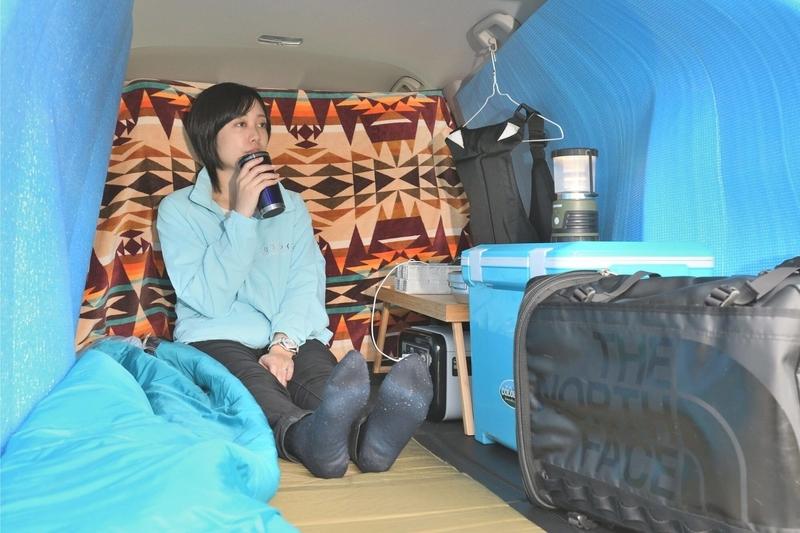 Hondaシャトルの荷室をひとり用の車中泊仕様にして女性がくつろいでいる写真