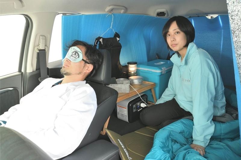 hondaシャトルの車内を車中泊仕様にしたところに女性がひとり座り、運転的にCar寝る博士がアイマスクをして寝ている写真