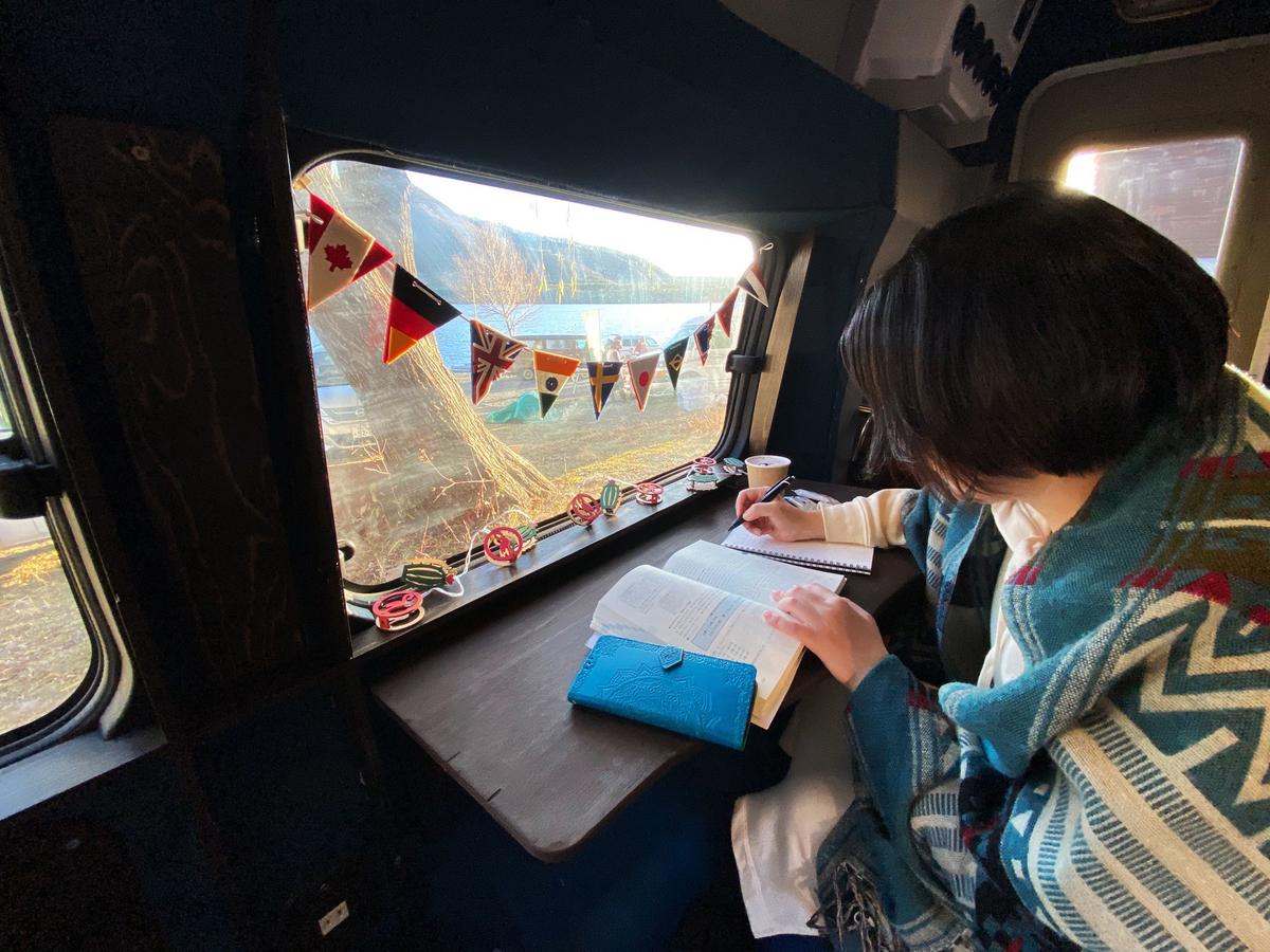 宮下佳織さんがガーランドがついた窓のある車内で書き物をしている写真