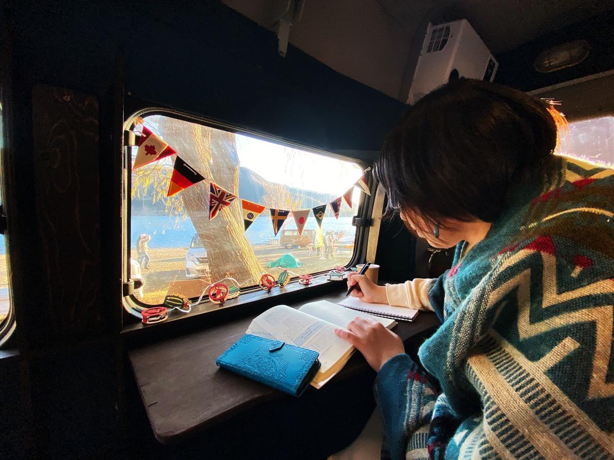 宮下佳織さんが窓にガーランドが付いた車内で書き物をしている写真