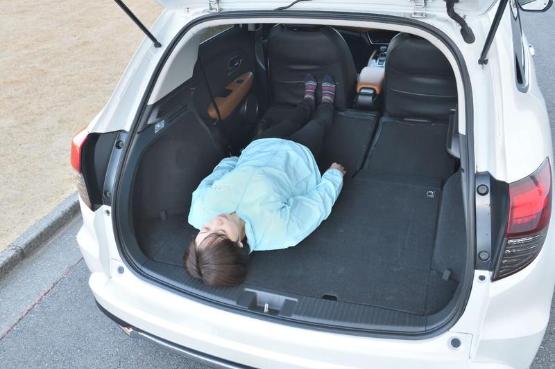 ヴェゼルの後部座席を倒してフラットにした荷室に女性が寝ている写真