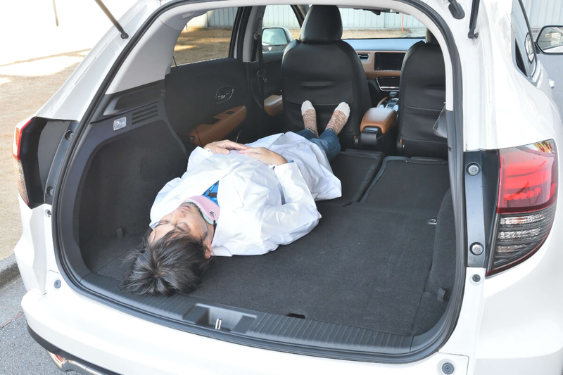 ヴェゼルの後部座席を倒してフラットにした荷室に男性が寝ている写真