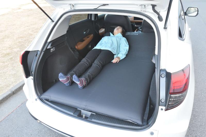 エアマットを敷いたヴェゼルの車内に女性が寝ている写真