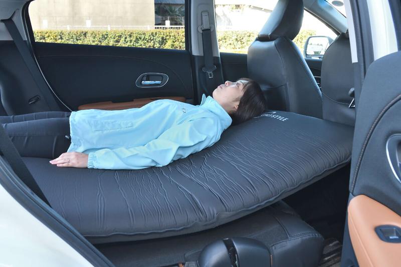 エアマットを敷いたヴェゼルの車内に女性が寝ているのを横から撮った写真