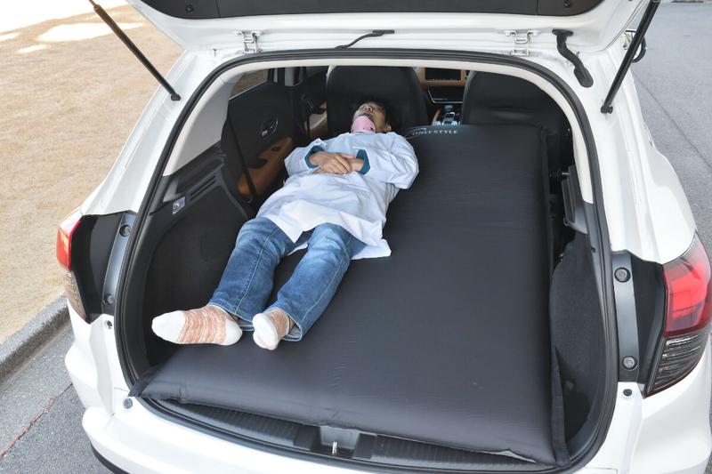 エアマットを敷いたヴェゼルの車内に男性が寝ている写真