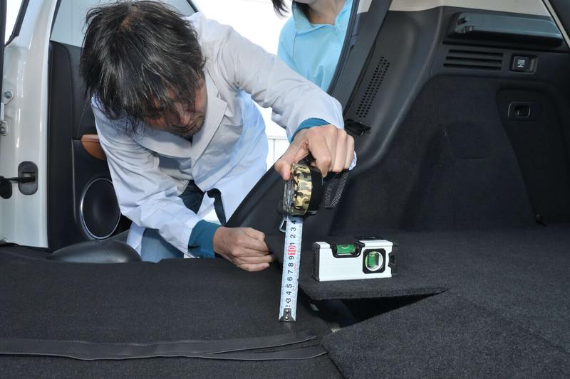カーネル博士が水平器を使ってヴェゼルの車内の傾斜を調べている写真