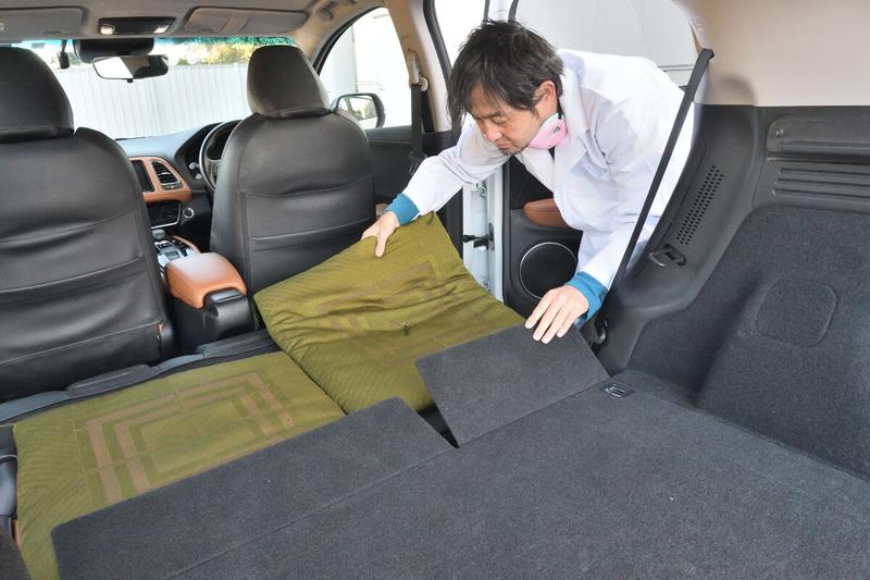 ヴェゼルの後部座席を倒してフラットにした荷室に座布団を敷いているカーネル博士の写真
