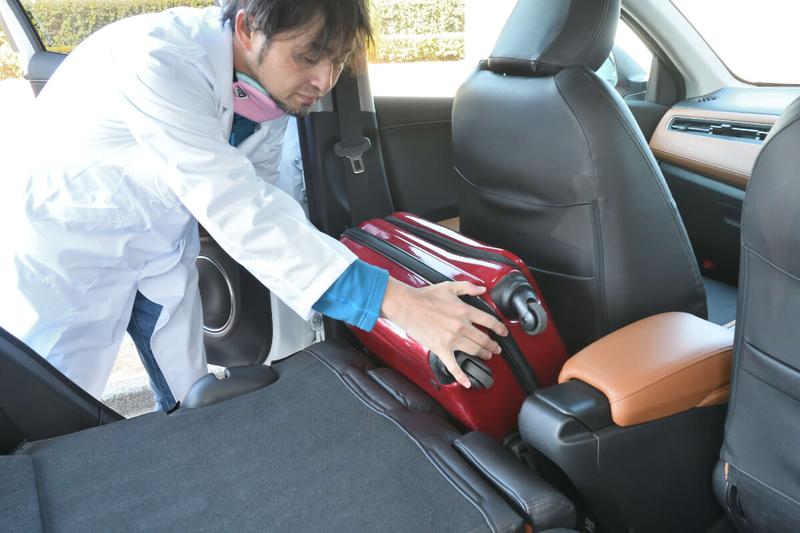 前座席と後部座席の間にできた隙間をスーツケースで埋めている写真