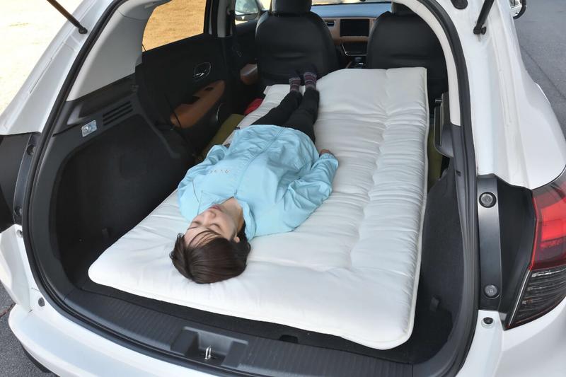 フラットにして車中泊仕様にしたヴェゼルの車内にニトリのシングルサイズの布団を敷いて、その上に女性が寝ている写真