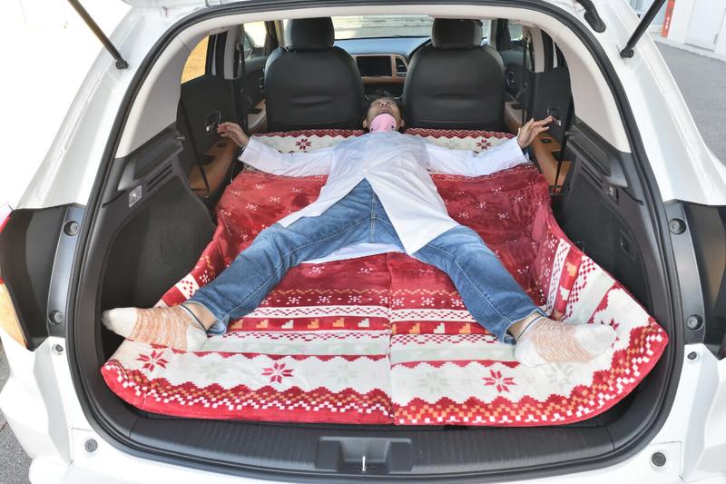 フラットにして車中泊仕様にしたヴェゼルの車内にお昼寝用のマットを敷いたところに男性が大の字で寝ている写真