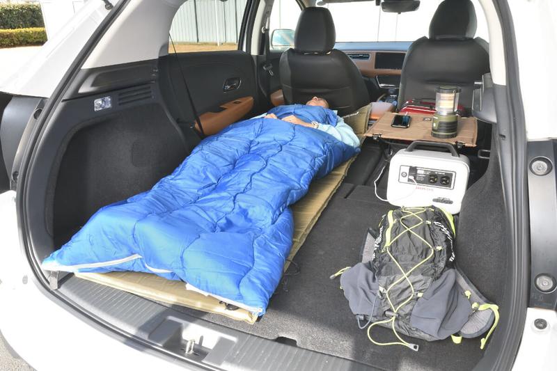 ヴェゼルの後部座席を片側だけ倒して一人用の車中泊仕様にしたところに寝袋を使って女性が寝ている写真