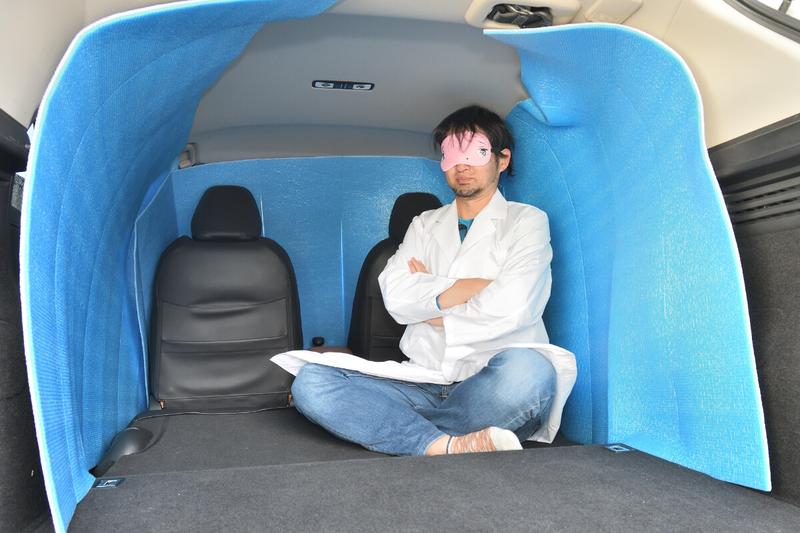 車中泊仕様にフラットにしたヴェゼルの荷室を銀マットを使って目隠しシェードを作ったところに男性があぐらをかいて座っている写真