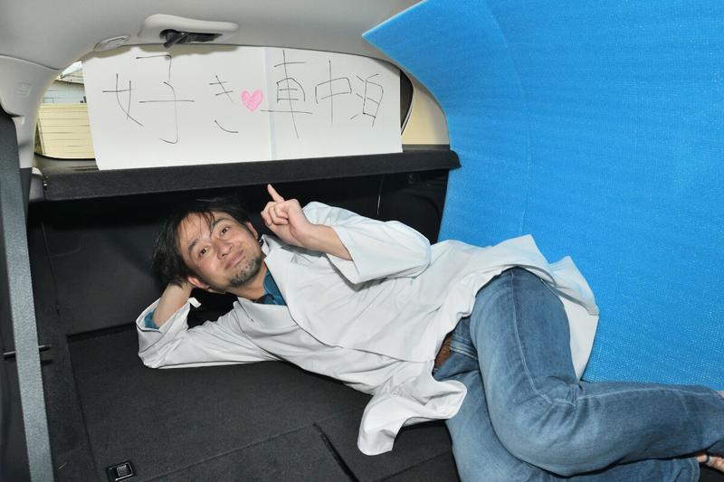 車中泊仕様にフラットにしたヴェゼルの車内で男性が寝ている写真