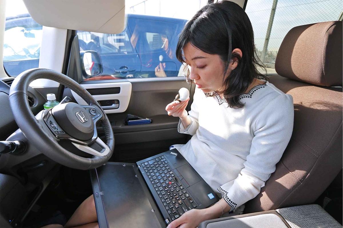 車内でパソコンを開いて、アロマモーメントのディフューザーキットを鼻に近づけるなぎささん
