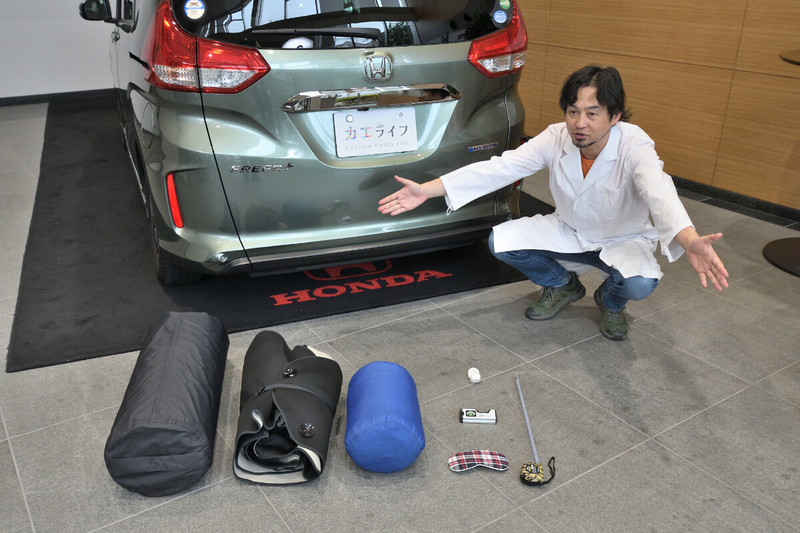 カーネル博士がフリードプラスのリアゲートの前で車中泊の7つ道具を広げている写真