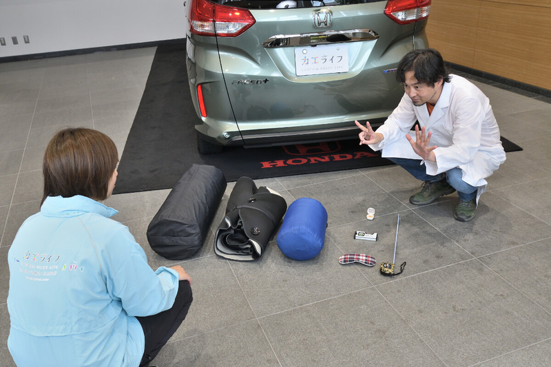 カーネル博士が車中泊の7つ道具を前にしている写真