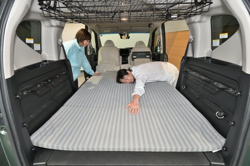 フリードプラスの2列目シートを倒してフラットにした車内荷室に純正アクセサリーのラゲッジクッションマットを敷いた上に、Car寝る博士(カーネル博士)が寝ている写真