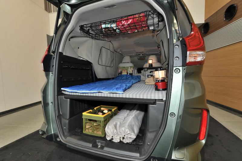 フラットにしたフリードプラスの車内荷室:プライバシーシェードを使って窓を目隠しし、寝袋やポータブル電源が置いてある写真