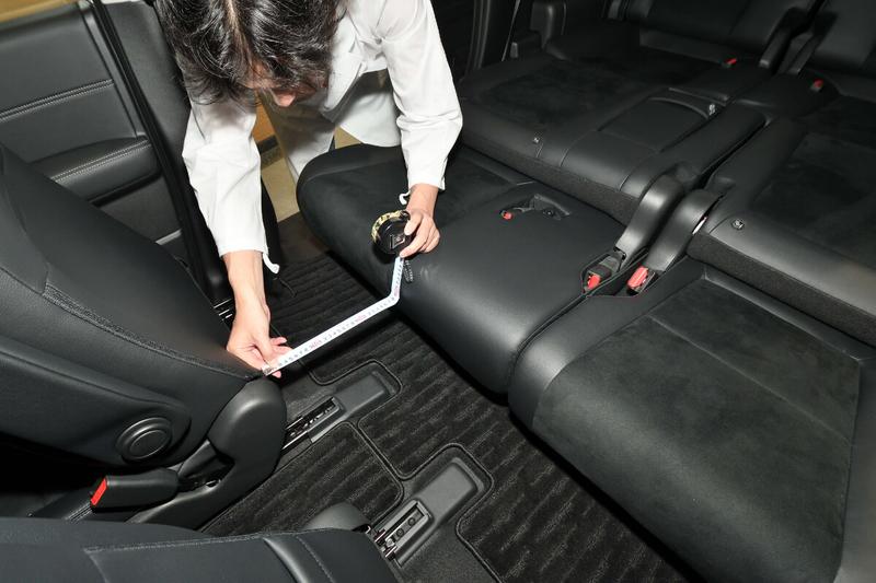 フリードの2列目を一番後ろにスライドさせたときに、1列目(運転席・助手席)との間にできる隙間の大きさを測っている写真