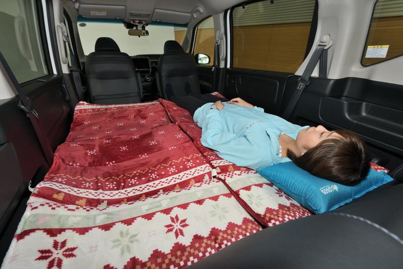 フラットに車中泊仕様にしたフリードの荷室車内で身長163㎝の女性が寝ている写真