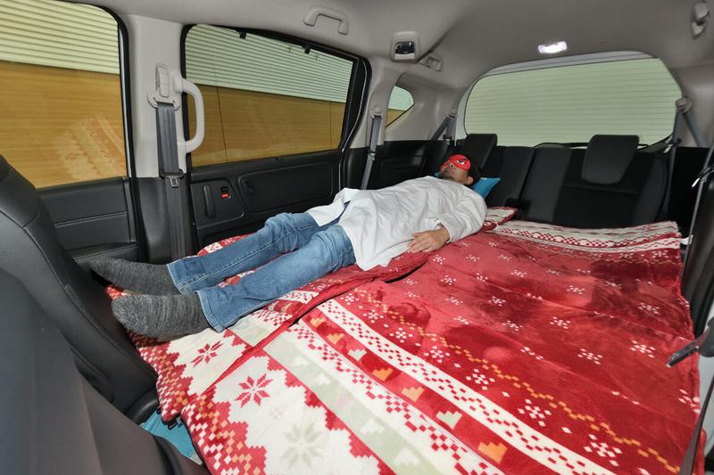 フラットにして車中泊仕様にしたフリードの荷室車内で身長175㎝の男性が寝ている写真