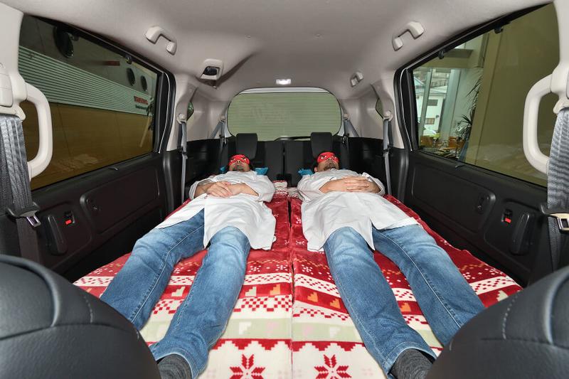 フラットにして車中泊仕様にしたフリードの荷室車内で身長175㎝の男性が2人寝ている写真
