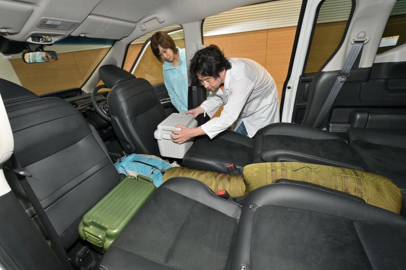 フリード(キャプテンシートタイプ)の2列目と最前列(運転席・助手席)の間にできた隙間を収納ケースやリュックで埋めている写真