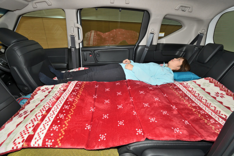フラットにして車中泊仕様にしたフリード(キャプテンシートタイプ)の荷室車内で身長163cmの女性が寝ている写真