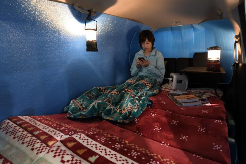 フラットにして車中泊仕様にしたフリードの車内荷室で、銀マットをカーテン替わりにしている写真