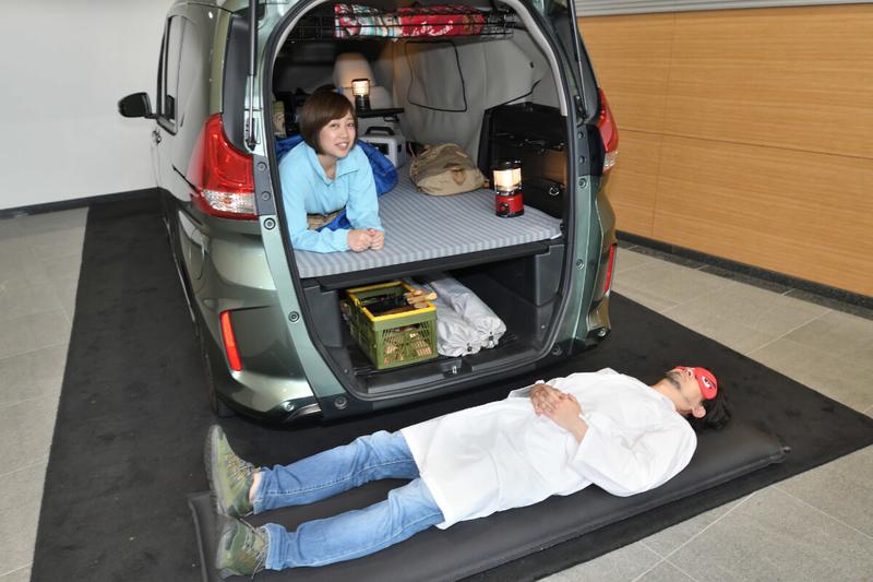 フリードプラスのリアゲートがあいていて、車中泊仕様の車内が見えている下で、カーネル博士が寝ている写真