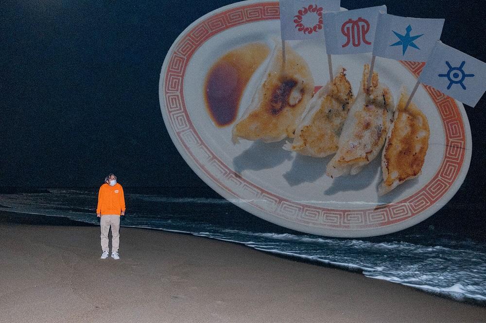 海と餃子を眺めている地主さんの写真