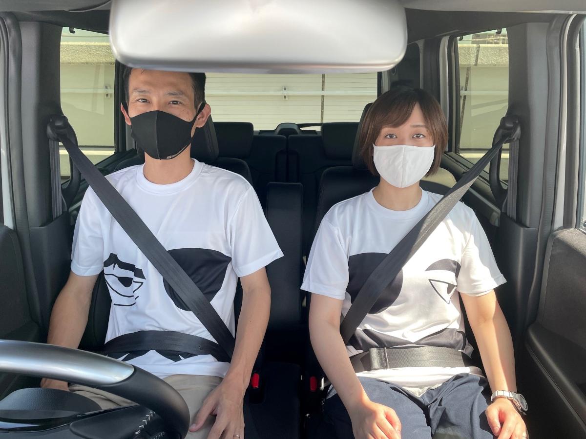 シートベルトが似合うTシャツコンテストの【社長賞】の実物のTシャツを着て運転席・助手席に座っている写真
