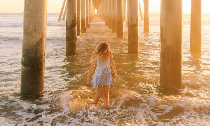 女性が橋の下で波と遊ぶ