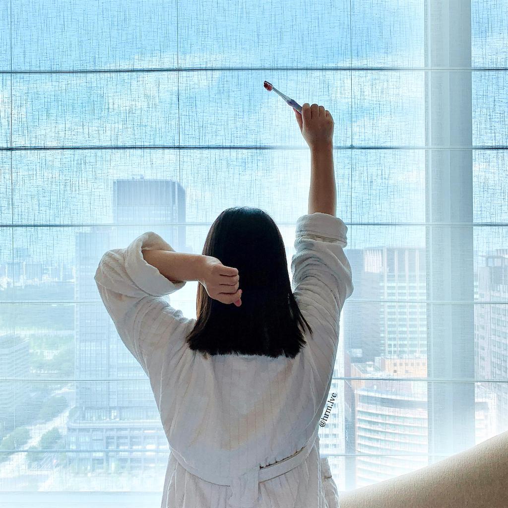歯ブラシを持って窓辺に向かって伸びをする女性