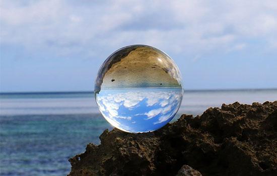 海辺に置かれた神秘的な水晶だまの画像