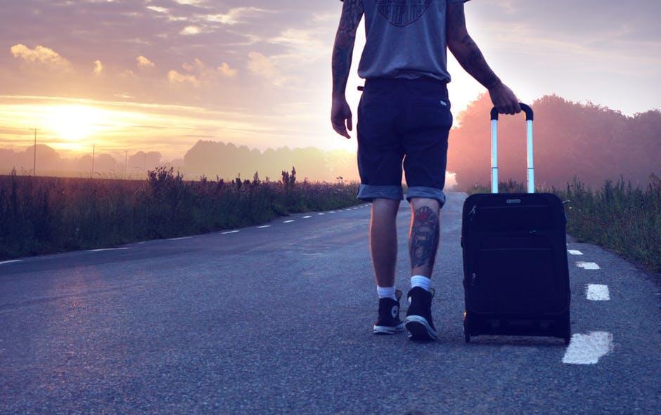 男性がスーツケースを引く画像