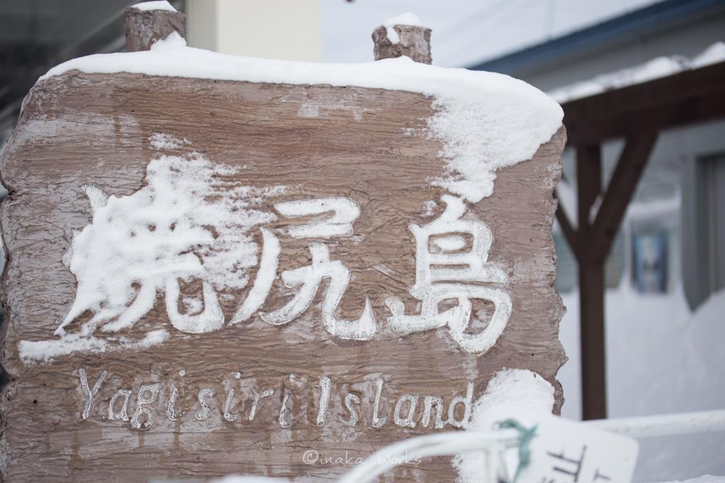 雪がこびりつく焼尻島の看板
