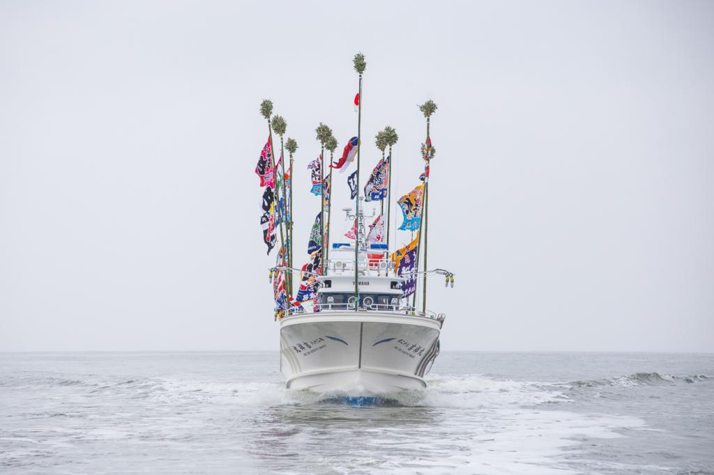 日本海に浮かぶ新造船を正面から日の丸構図