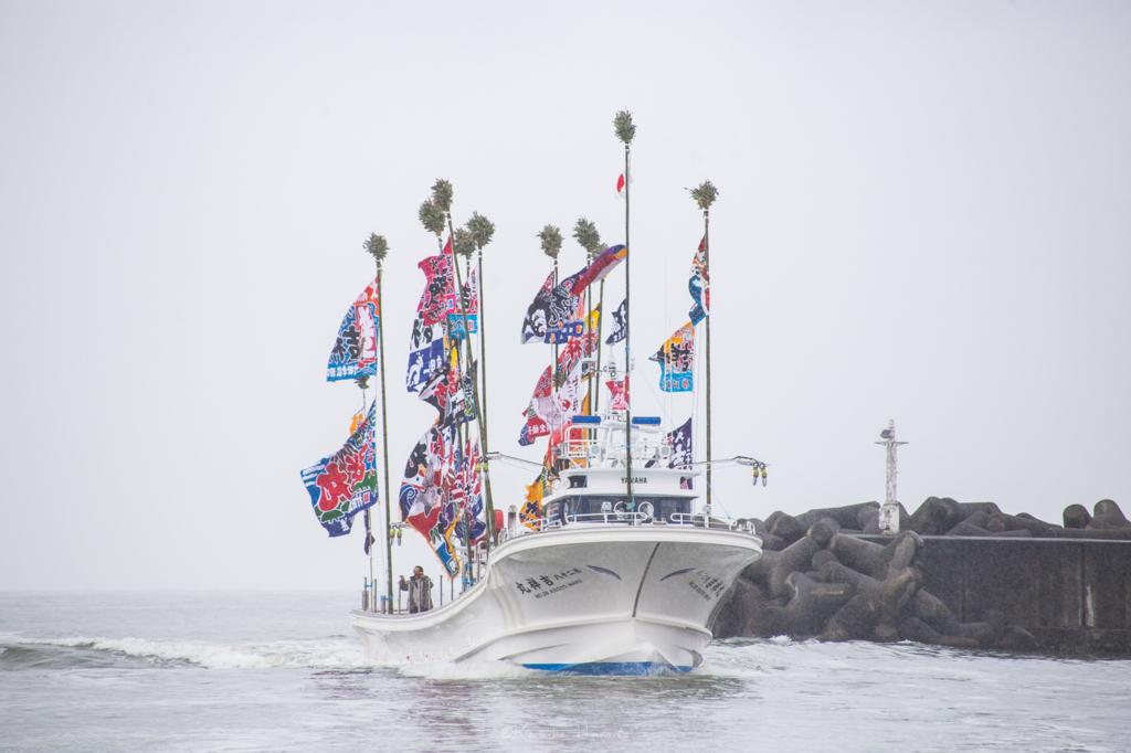 日本海に浮かぶ新造船を正面から灯台と