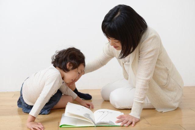 女の子とお母さんが一緒に本を読んでいる画像
