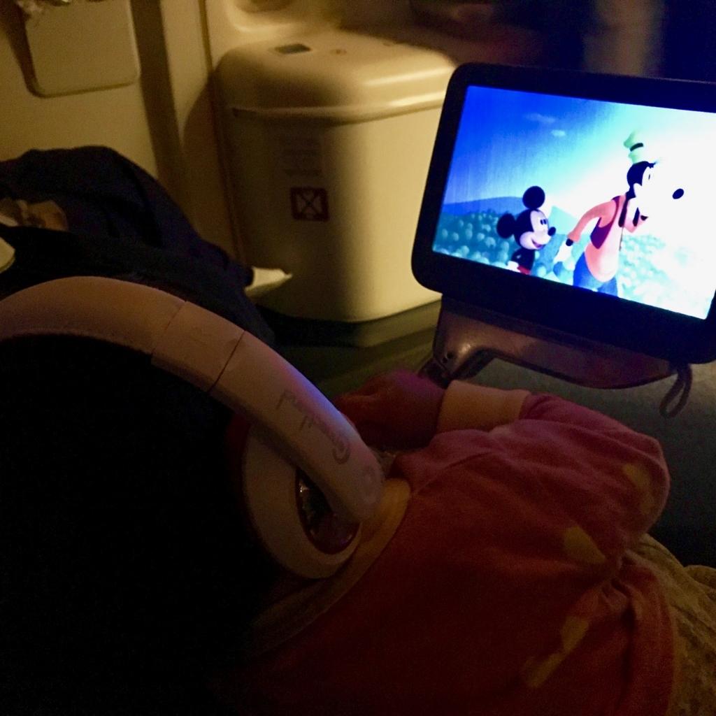 子供用ヘッドフォンで機内動画鑑賞する1歳児