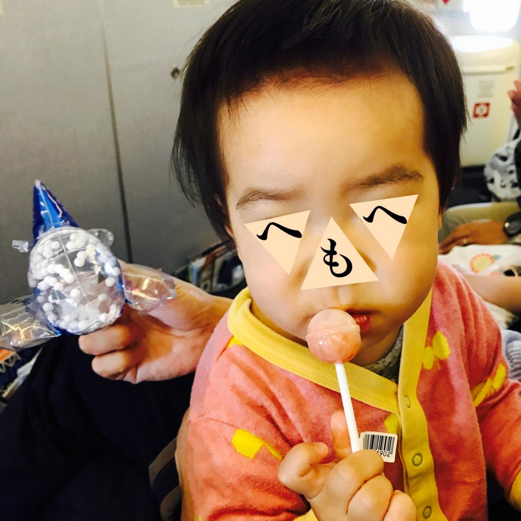 飛行機内で棒付きキャンディーを食べる長女