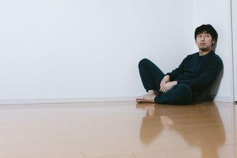 なにもない部屋で1人座る男性。