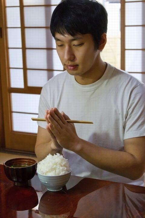 食事を前に手を合わせる男性。