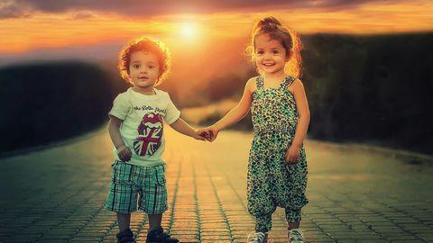 手をつなぐ幼い男の子と女の子。