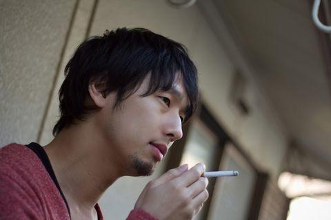 ベランダでタバコを吸うイケメン男性。