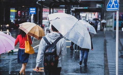 傘をさして歩く人々。
